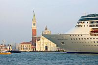 Venice (Italy). Bow of ocean liner next to the island of San Giorgio Maggiore next to the city of Venice.