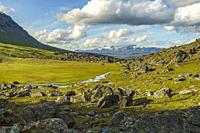 Hiking trail at Kärkevagge, Swedish Lapland with big rocks and river floating and mountains in background and cloudy weather, Kiruna county, Swedish L...