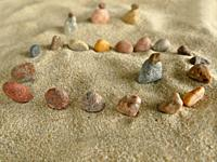 symbolic picture of isolation with stones in sand.