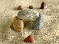 symbolic picture of going through a gate with stones in sand.