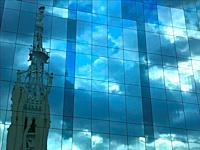 Bell tower and sky reflected on glass facade. Goya street, Madrid, Spain.