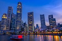 Singapore. Quay with cafes and skyscrapers. Pleasure boats. Dusk.