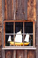 Model boat on display in the window of a workshop at the Britannia Ship Yard site in Steveston British Columbia Canada.