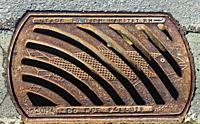 Cast Iron drain cover with a fish emblem and a warning not to pollute.