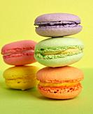 stack of baked macarons on a yellow green background, delicious dessert made from almond flour, close up.