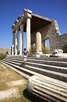 Tourist woman standing in front of Ionic Stoa-stone temple in the ancient ruins of Miletus, Miletos, Milet, Aydin Province, Turkey, Europe