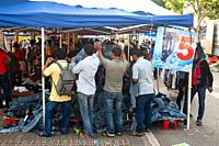 Singapore, Republic of Singapore, Asia - Men of South Asian origin rummage for trousers and blue jeans at a street stall in Little India.