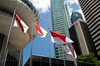 Singapore, Republic of Singapore, Asia - National flags wave in the city centre with the skyscrapers of the central business district in the backdrop....