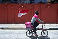 Singapore, Republic of Singapore, Asia - A delivery rider who works for the food delivery service Foodpanda wears a protective face mask to protect hi...