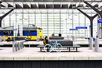 Rotterdam, Netherlands. Girl with Blue Bike waiting on a Rotterdam Centraal Railway Station´s platform for her connecting train, while mounting her ma...