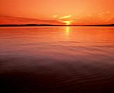 Sun setting over calm smooth Lake Superior in the upper Peninsula of Michigan in the United States.