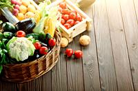Basket of Organic Vegetable Food Ingredients and crates of potatoes and tomatoes on wood background.