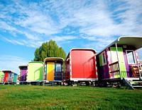 Multi color caravans against blue sky.