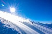 Steep ski slope in windy sunny weather. A lonely unrecognizable snowboarder descends and picks up a lot of snow dust in the backlight of the sun.