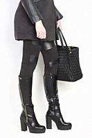 fashionable black boots with a handbag.