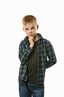Portrait of a pensive boy in a plaid shirt on a white background.
