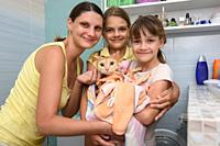 Family poses in the bathroom with wet bathed cat wrapped in towel.