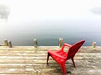 A red chair on the dock in a cove at the edge of the Atlantic Ocean, Halifax, Canada. Ideal spot for meditation, reflection, or vacation by the sea.