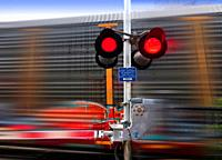 A train speeds past a railway crossing barrier, red lights flickering, Ontario, Canada.