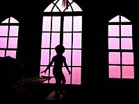 A young kid standing in a sporting posture in an attic with glass windows, Nova Scotia, Canada.