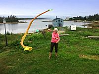 A sprightly senior woman playing with a Chinese kite called the Dancing Dragon, Halifax, Nova Scotia, Canada.
