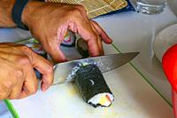 Making sushi rolls at home in the kitchen and cutting.