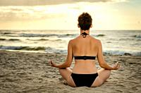 beautiful woman in a black swimsuit meditating on the beach at sunset.
