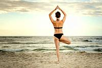 beautiful woman in a black swimsuit practicing yoga on the beach at sunset.