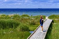 Falsterbo, Sweden A woman on a boardwalk at the seashore in the Flommen nature reserve.
