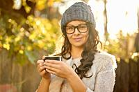 beautiful woman in a cap and glasses holds in her hand a cup of coffee in an autumn forest.