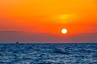 Boundless sea. Unbelievable orange sunset. Small freighter ship on the horizon.