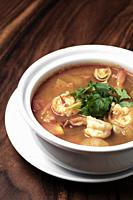 thai tom yum kung spicy and sour shrimp soup on wood table background in phuket thailand.