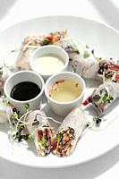 asian fresh vegetable vegan spring rolls with sauces in vietnam.