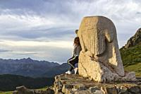 Woman enjoying the seated views of the Picos de Europa at the Llesba lookout next to the bear statue.