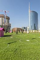 MILAN, ITALY - August 20 2020: cityscape with beach umbrellas on sunbathing ground on grass at business hub urban renewal development, shot on august ...