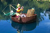 Fisherwoman in floating basket lantern in Dream Lake during the annual Magic of Lanterns exhibit in the Chinese Garden in autumn, Montreal Botanical G...