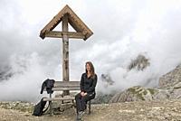 jeune femme assise sur un banc sous un crucifix sur le chemin reliant les refuges Locatelli (Dreizinnenhutte) et Pian di Cengia (Bullelejochhutte) , P...