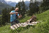 homme servant le vin au cours d'un pique-nique prepare par le chef etoile Chris Oberhammer du Restaurant Tilia a Dobbiaco, dispose dans un pre au-dess...