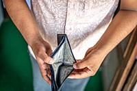 Man holds empty wallet. Bankruptcy and poverty concept. Unemployment during financial crisis. Genuine Leather written all over the interior of the wal...