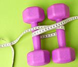 pair of purple dumbbells tied with a centimeter on a green background, body weight control concept, top view.