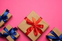 gift boxes wrapped in brown paper and tied with a red and blue bow, gifts on a pink background, place for text.