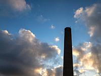 Tall chimney smokestack against cloudy sky