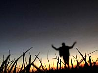 Silhouette of a person arms weaving at sunset
