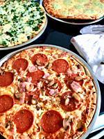 Close-up of three pizzas.