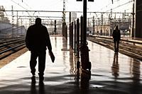 Two travelers wait in Atocha Renfe, train station, MADRID, SPAIN, EUROPE.