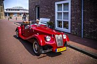 Man driving an oldtimer through the streets of Hellevoetsluis, The Netherlands, Europe.