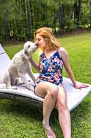 A 27 year old redhead woman with her dog in the backyard.