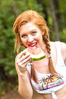 A happy 27 year old redhead woman eating a watermelon outdoors.