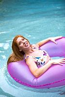 A 27 year old redhead woman in a swimming pool playing with a pink pool toy.