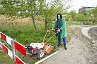 woman with street work machine constructing bike lane to reduce environmental pollution and emissions